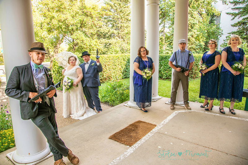 the wedding party stand on the front porch of Rutherford House - the guys holding their Tommy guns and the ladies looking beautiful