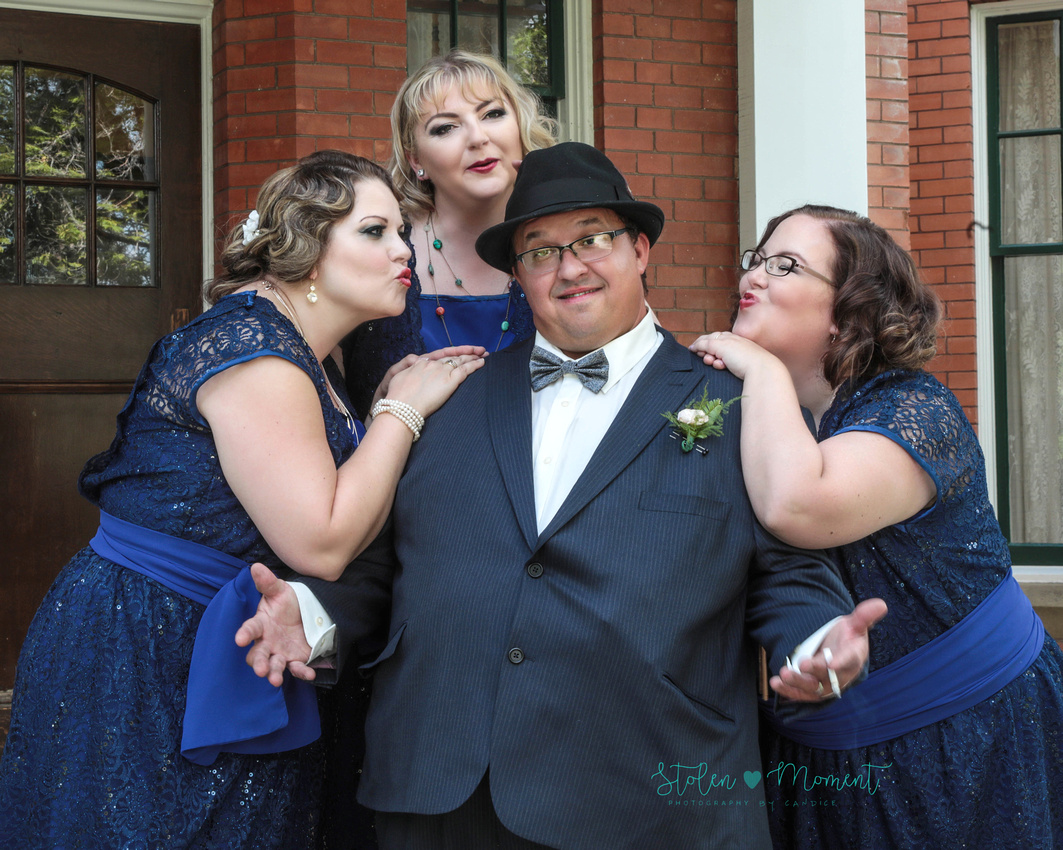 """the groom strikes a """"I'm the man"""" pose while the three bridesmaids hang on him trying to kiss him"""