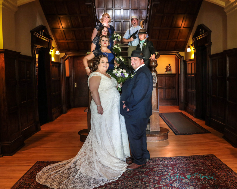the bride, groom and the five members of their wedding party stand on the stairs inside Rutherford House