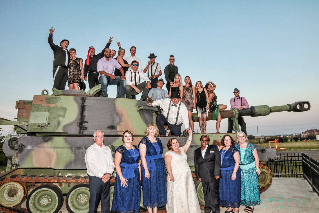 the entire wedding party and almost every guest pose on and in front of a large army tank outside the Kingsway Legion