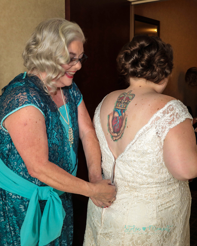 the bride's mom smiles as she does up the zipper on her daughter's wedding dress