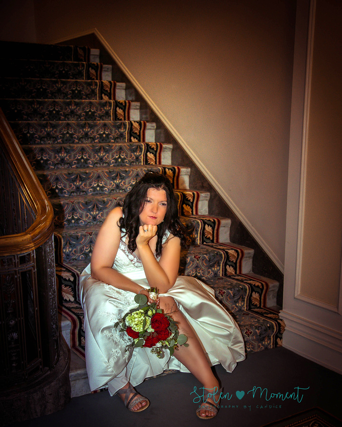 the bride strikes a sexy pose on the stairs in the lobby of the Fairmont Hotel MacDonald