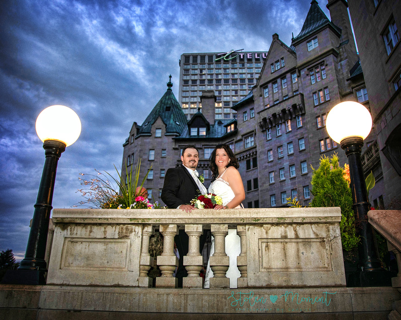 the bride and groom stand on the terrace of the Fairmont Hotel MacDonald in the evening with dark storm clouds over head
