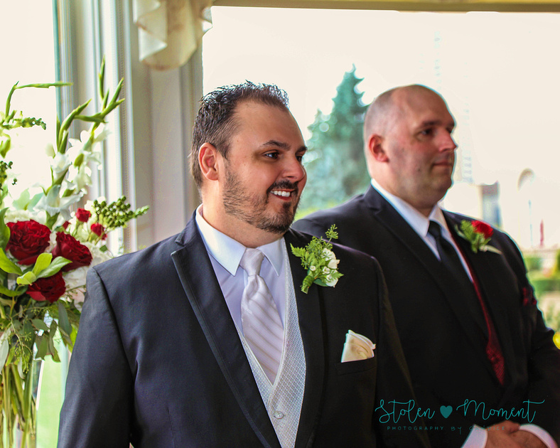 Groom sees his bride coming down the aisle and gets a nice smile on his face