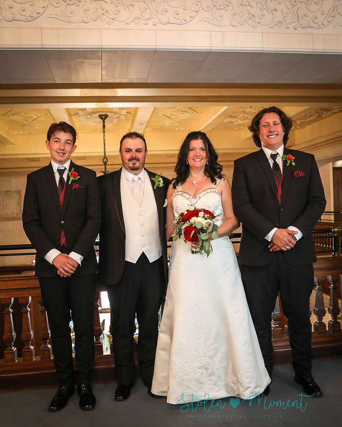 The bride and groom with the bride's two sons standing on the mezzanine level of the Hotel MacDonald