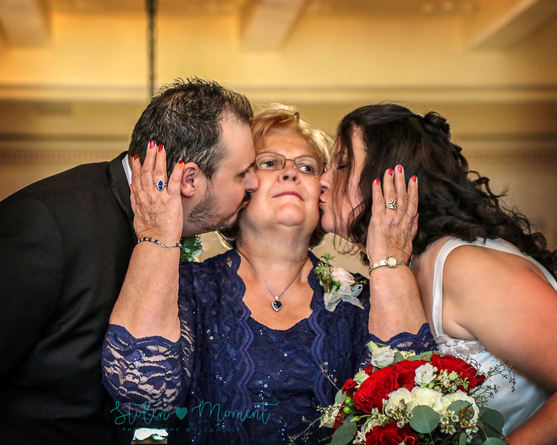 The bride's mom gets a kiss on her cheeks from both bride and groom