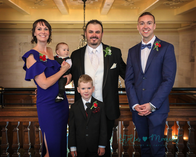 The groom stands on the mezzanine level of the hotel MacDonald with his sister, brother and two nephews