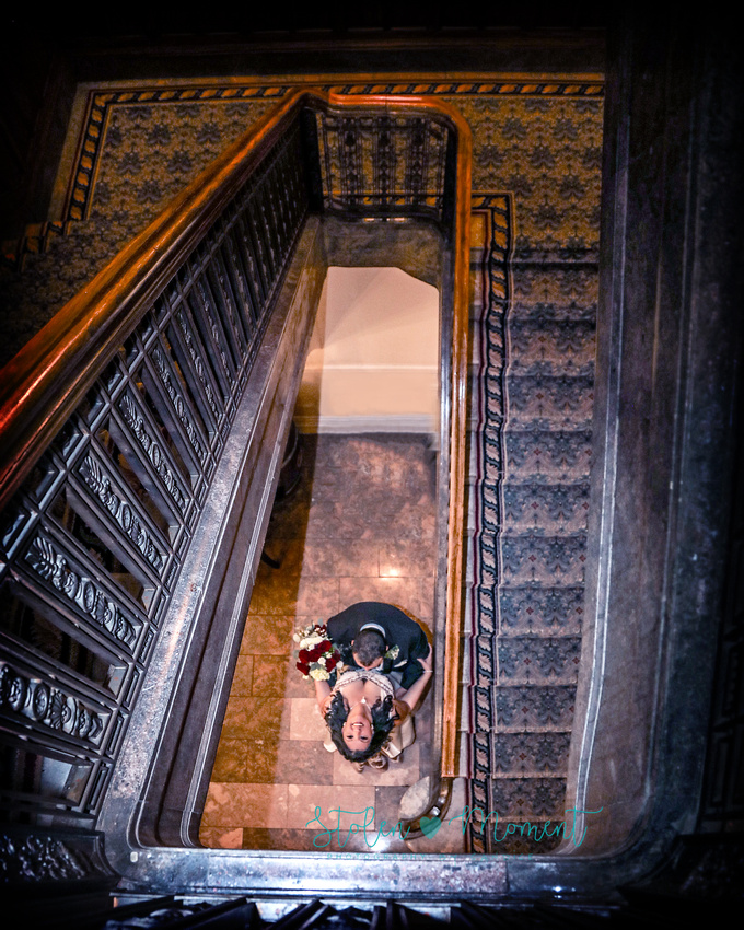 the groom is dipped by the groom at the base of the elegant staircase at the Hotel MacDonald in Edmonton