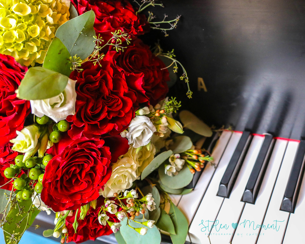 the bride's bouquet lays across the piano keys