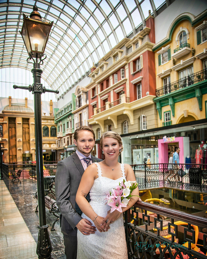 the bride and groom lean on a railing in front of a lamp post on Europa Blvd at West Edmonton Mall