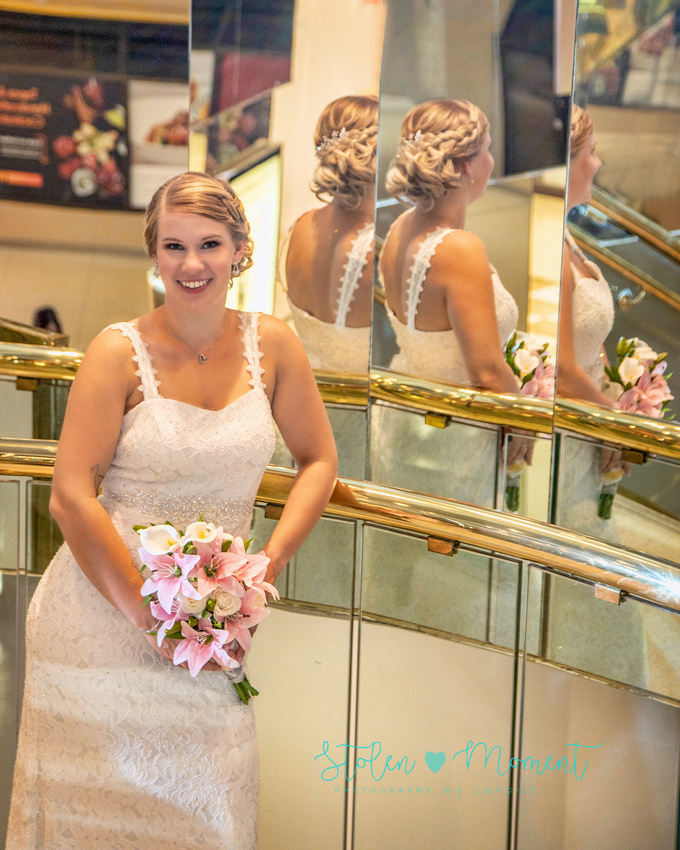 the bride leans on the railing on the stairs of Fantasyland Hotel with her back and hair reflecting in the mirrors behind her