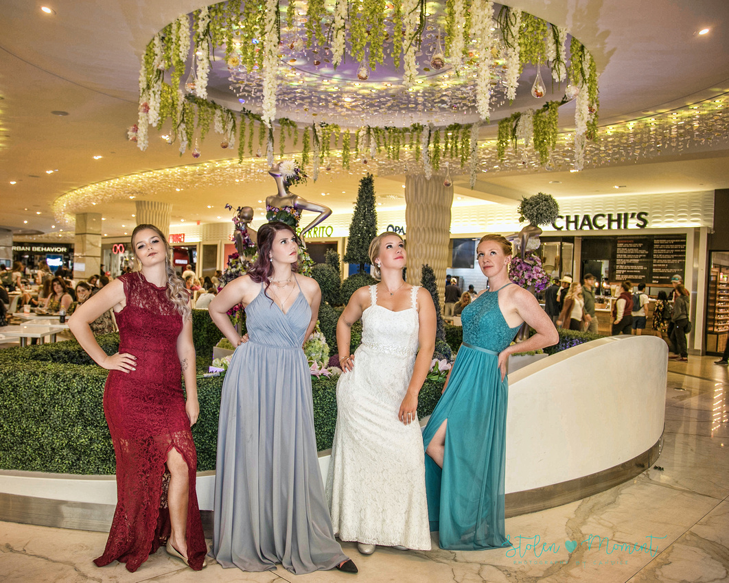 the bride and her three bridesmaids strike a pose to imitate the statutes behind them in the food court at West Edmonton mall
