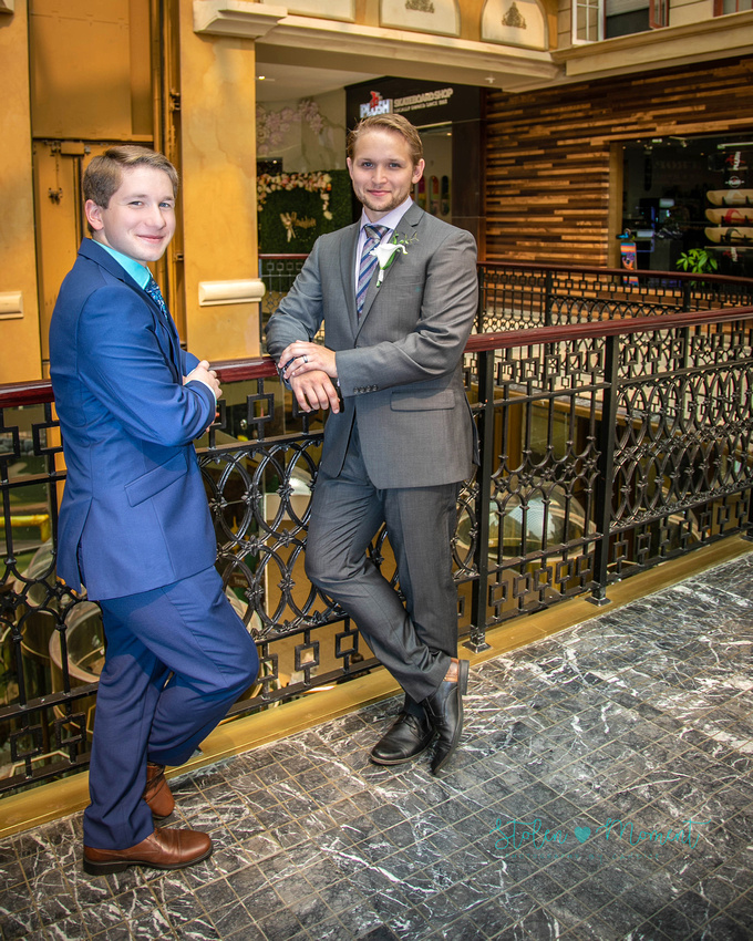 the groom and his best man/brother lean on the railing in Europa Blvd at West Edmonton Mall