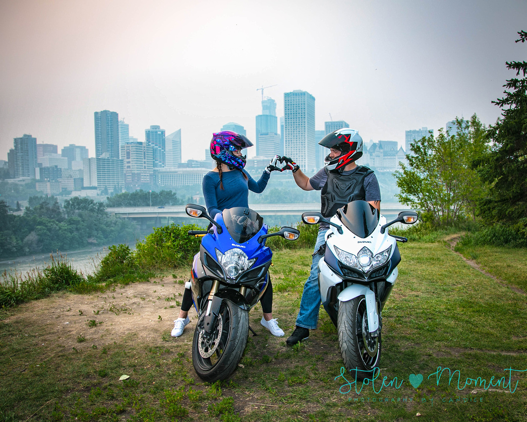 a couple sit on their Suzuki bikes with helmets on and make a heart with their gloved hands