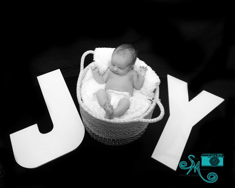 "A baby in a basket represents the letter ""o"" in the word ""Joy"""