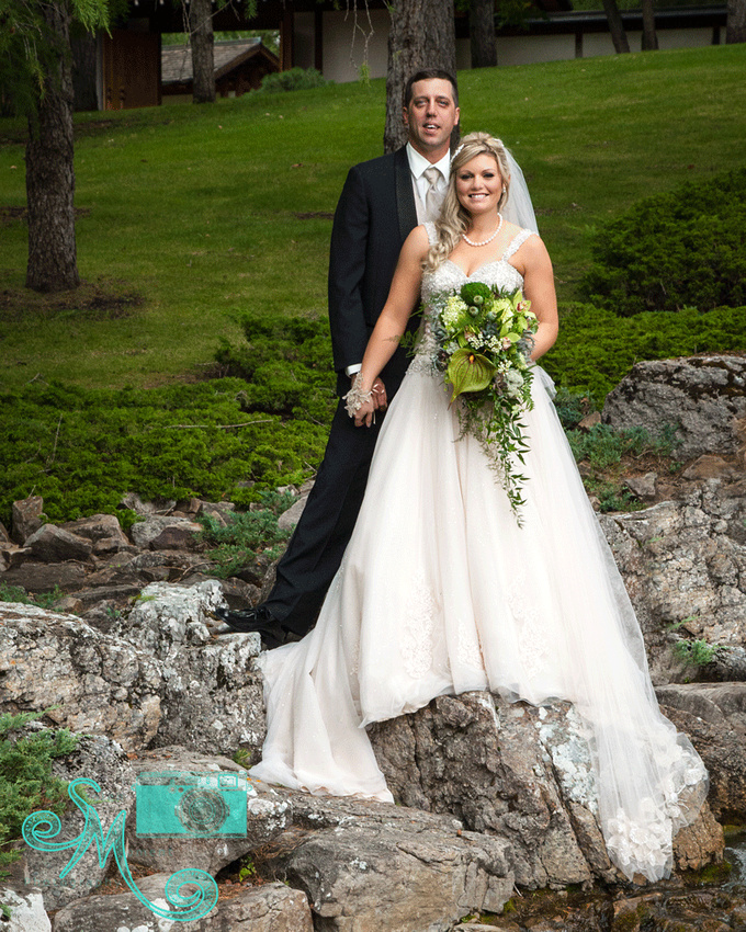Bride and groom holding hands standing on rocks by waterfall in Devonian Gardens