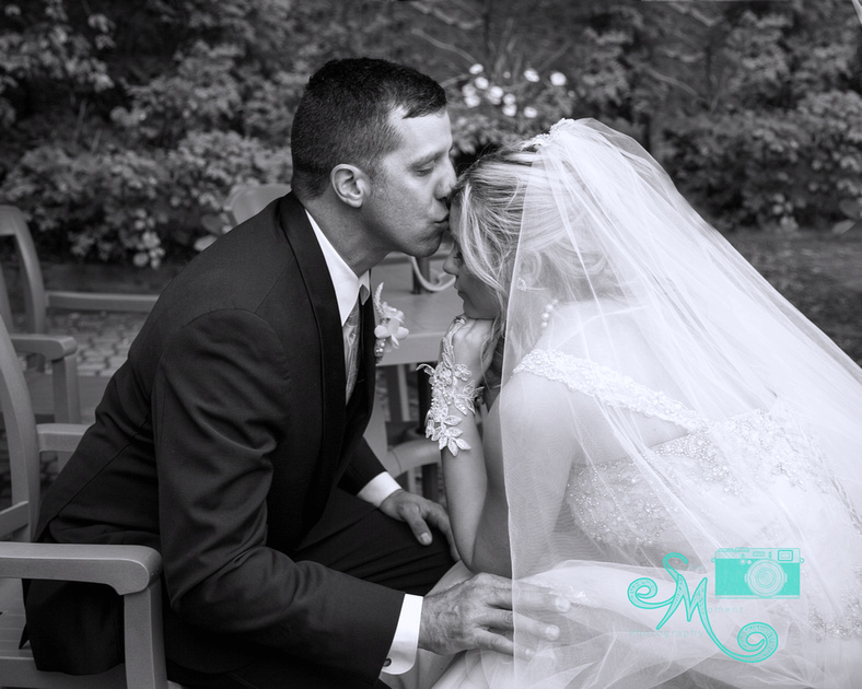 bride and groom sitting across from each other and groom leans in to kiss bride on forehead