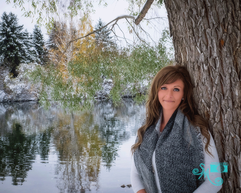 A lady poses against a tree in the winter with the lake in the background at Hawrelak park