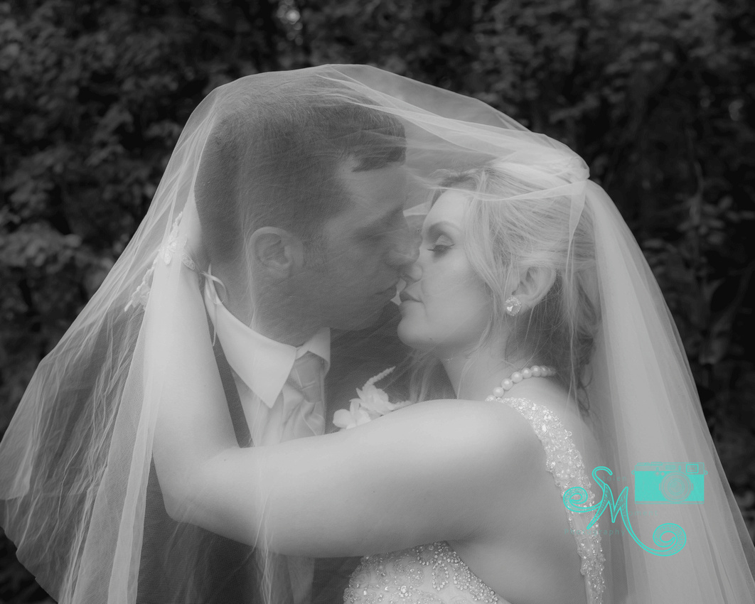 black and white photo of bride and groom about to kiss under her veil