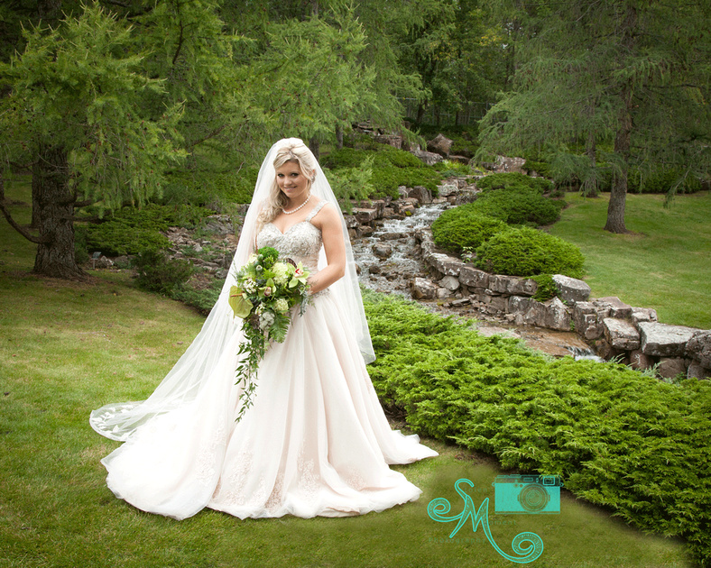 a beautiful bride stands in front of the falls at the Japanese Gardens