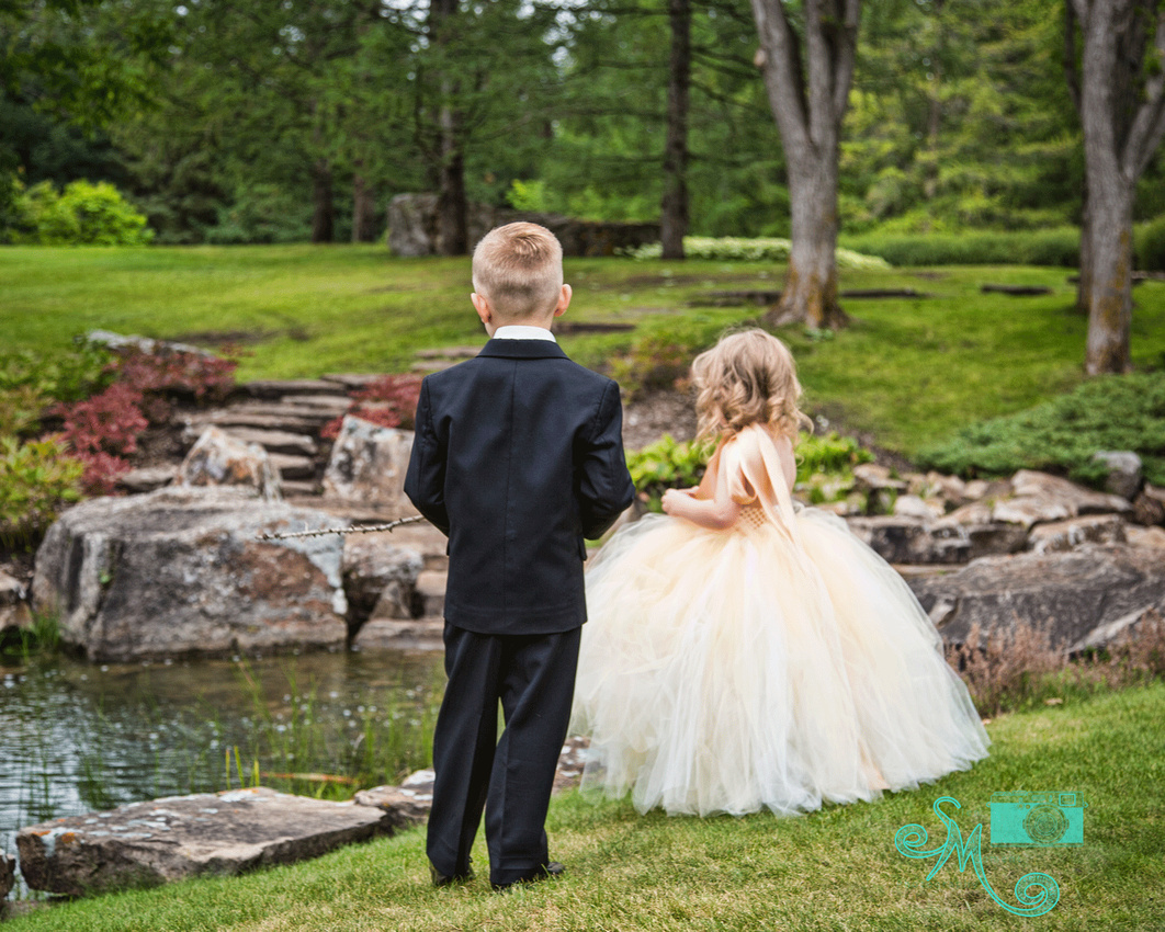 ring bearer and flower girl standing looking at water