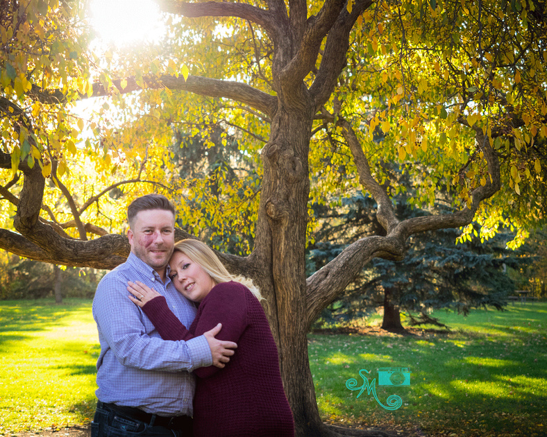 A woman lays her head on her fiance's chest while standing in front of a tree at hawrelak park