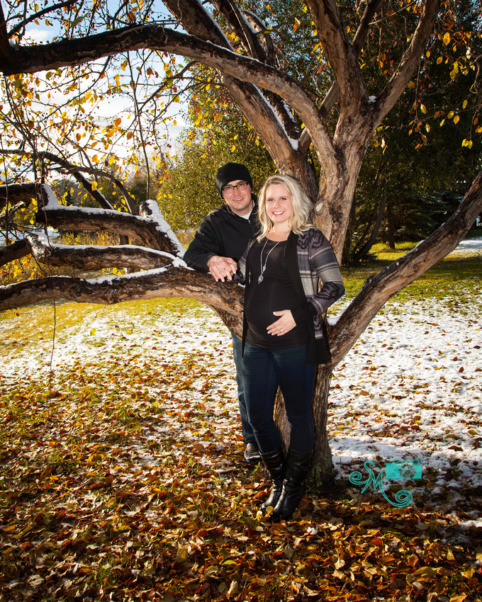 a man and his pregnant wife stand at a tree partially covered in snow with fall leaves on the ground