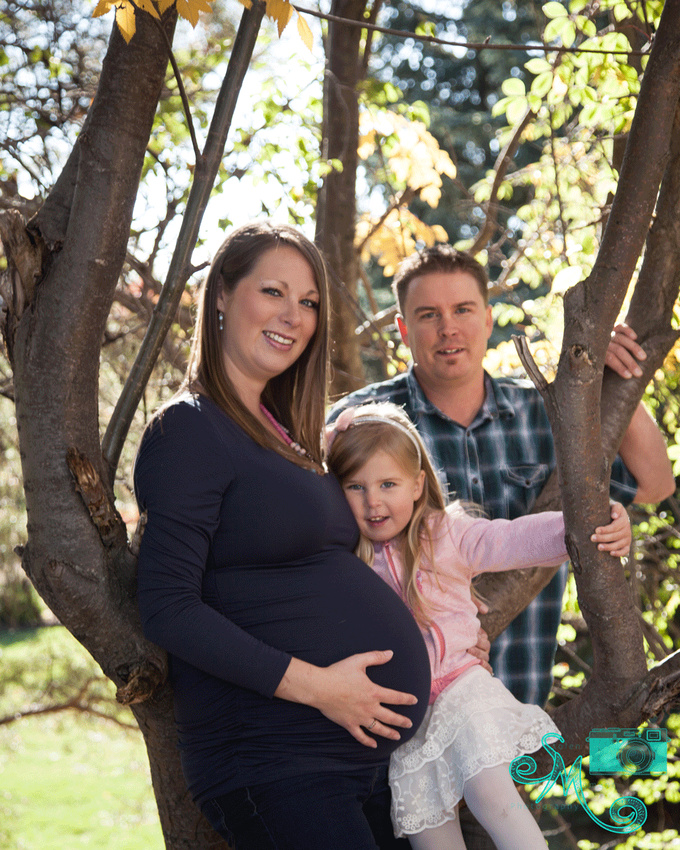 dad, pregnant mom and first born pose against a fall tree