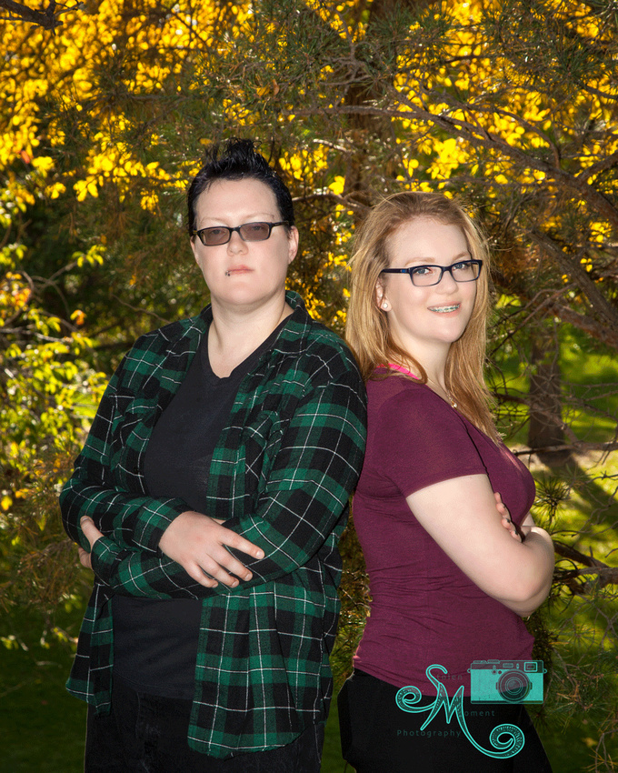 Two sisters pose back to back in front of some beautiful fall trees