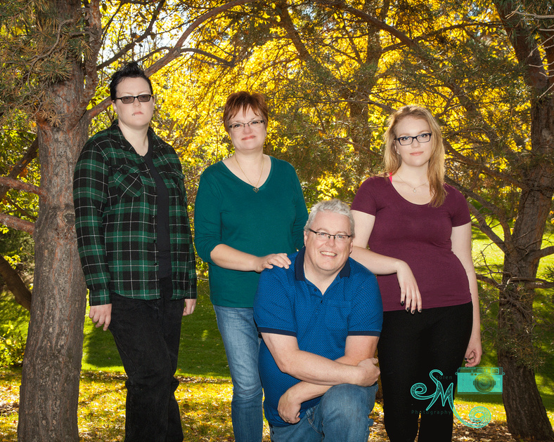 Family of four posing in front of a bunch of yellow coloured trees