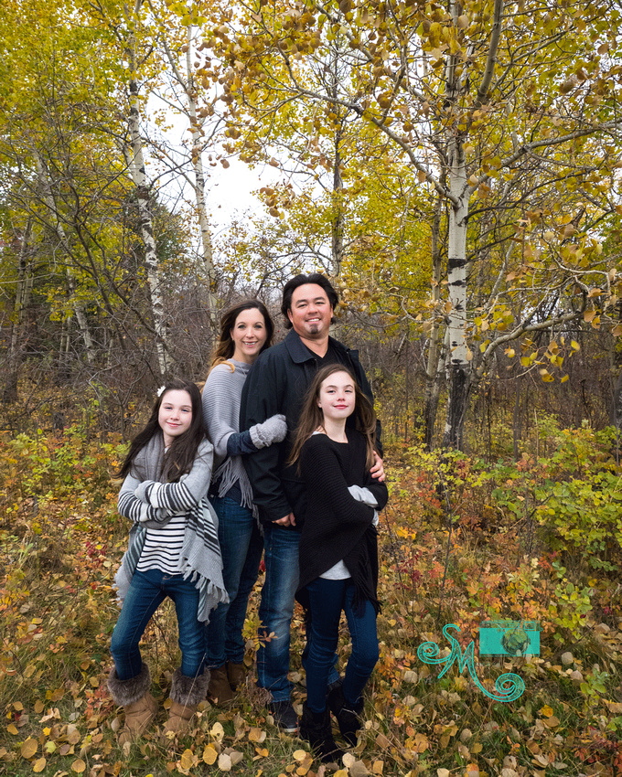 a family of four stand amongst fall coloured trees in Sherwood Park