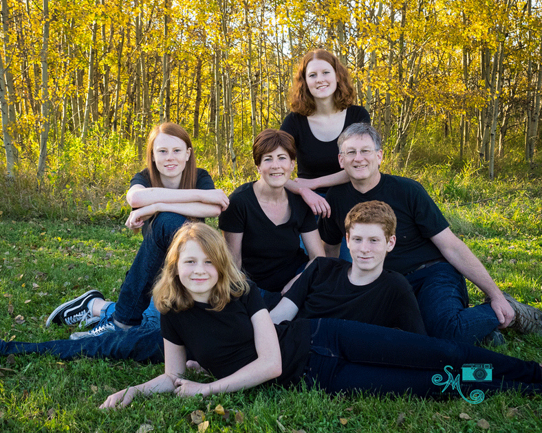 a family of six poses on the grass in front of a bunch of yellow leaved trees in Whitemud creek ravine in Edmonton