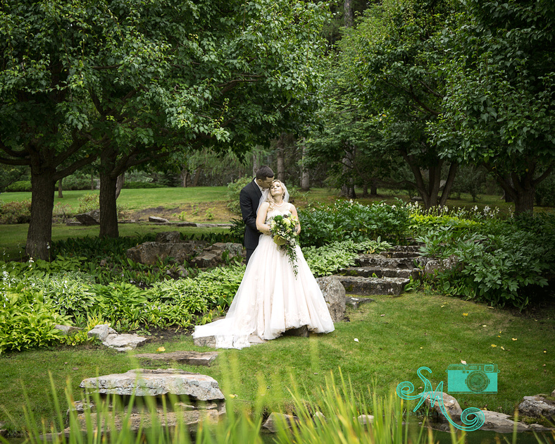 Bride and groom posing in an amazingly beautiful wooded, and rocky location at the Devonian Gardens