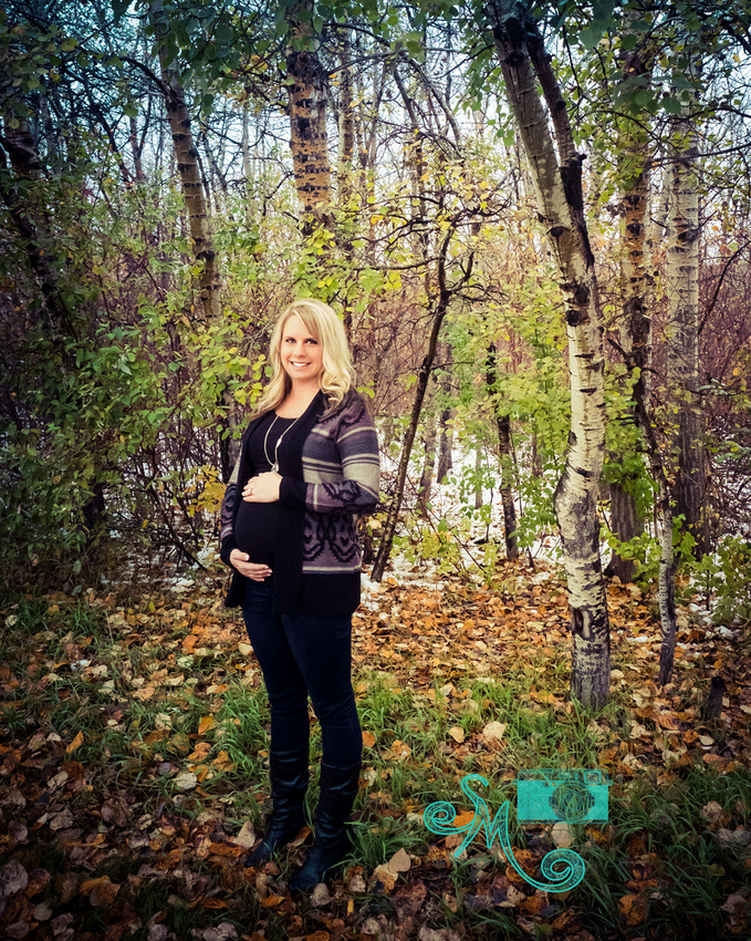 a pregnant lady stands in front of the fall leaves