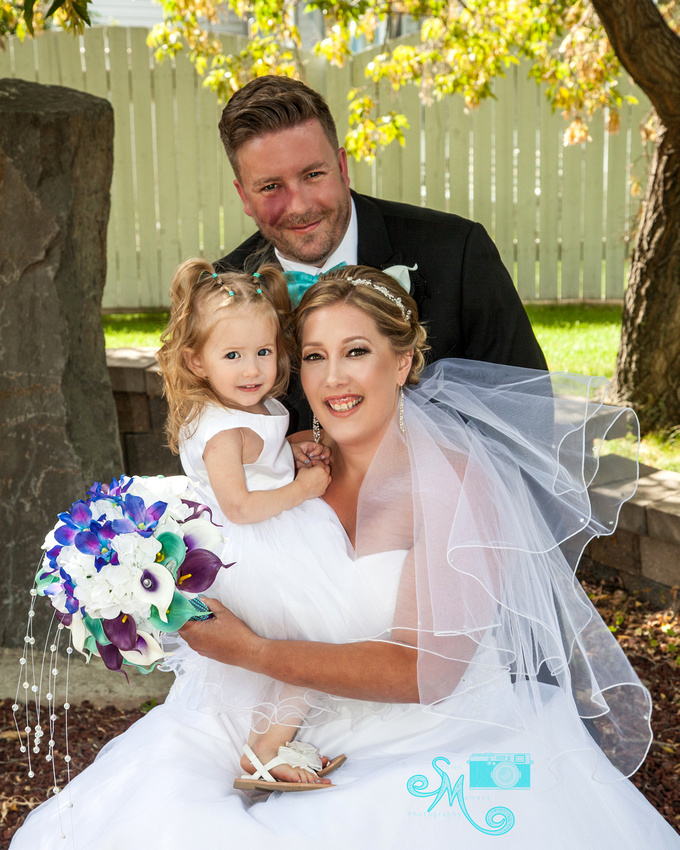A bride, her new husband and their beautiful little girl pose for a photo