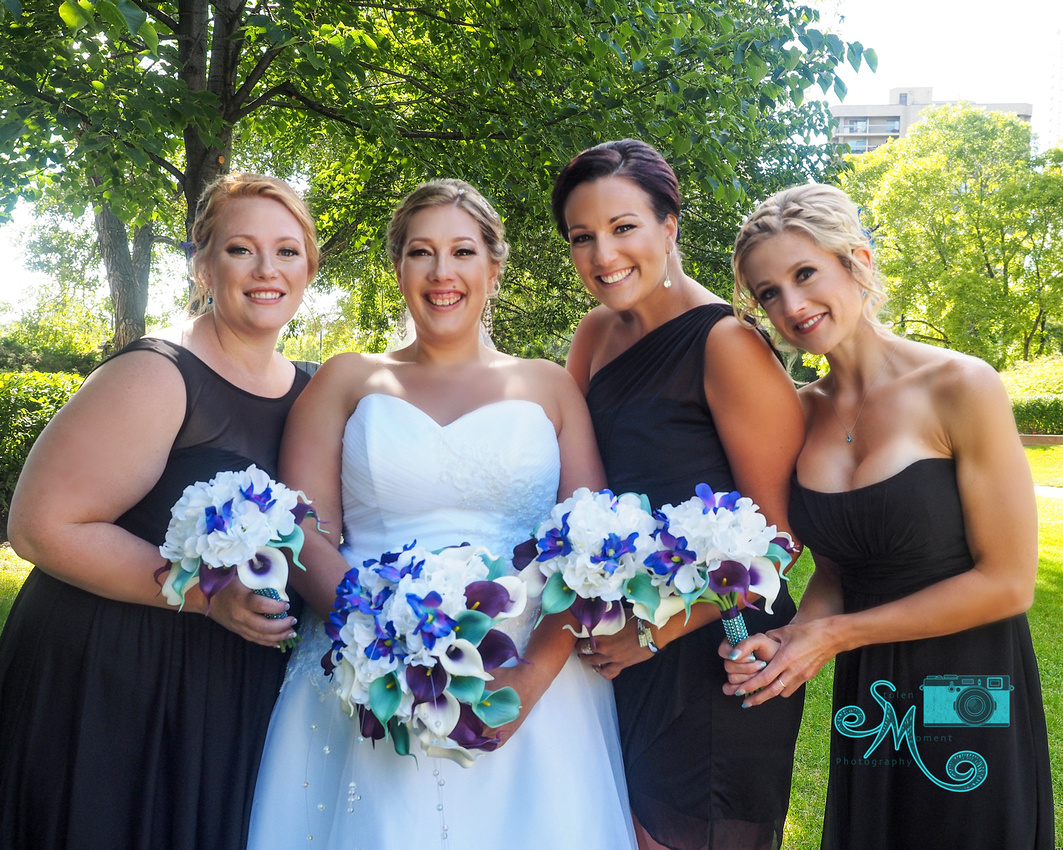 the bride and her girls pose in front of trees