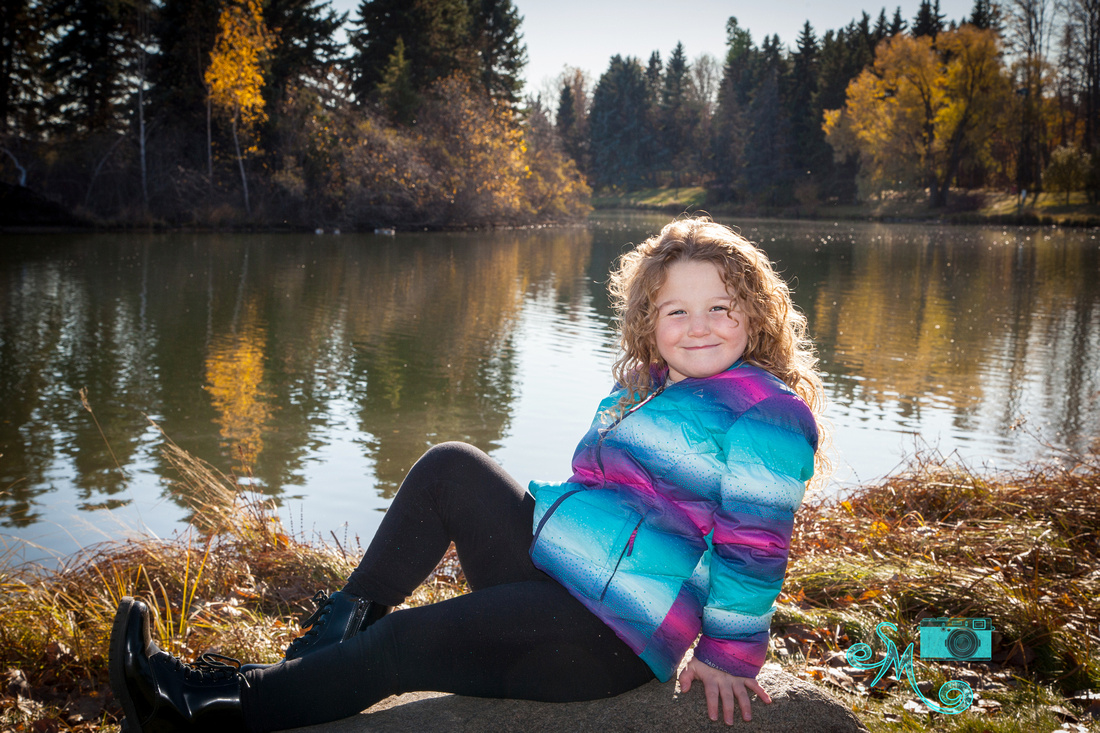 Adorable little girl poses on the rock in front of the lake at Hawrelak park