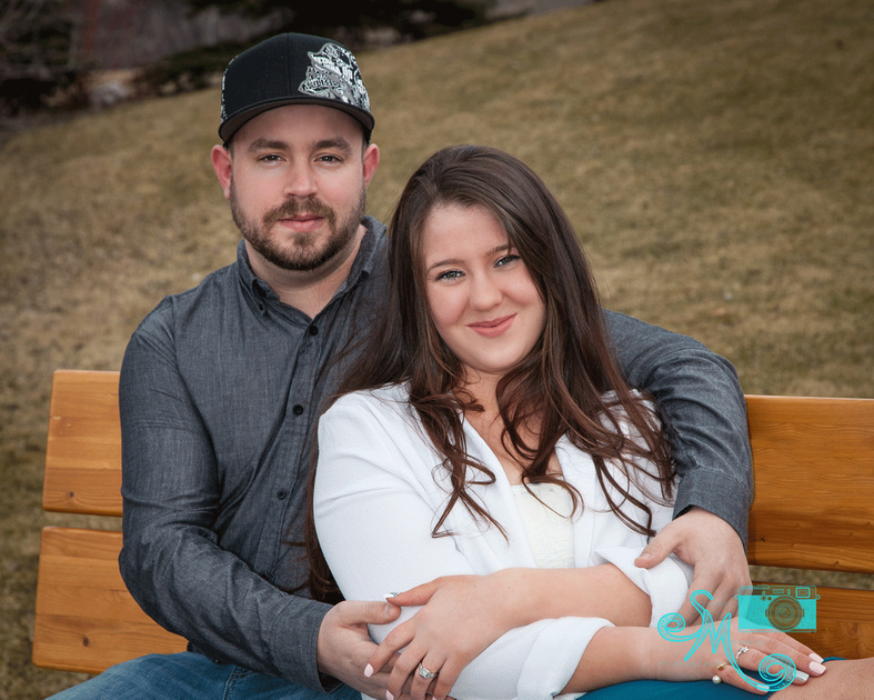 woman and her fiancé snuggle on a bench