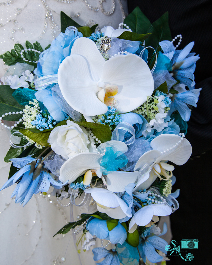 the bride's wedding bouquet with an owl pin in it