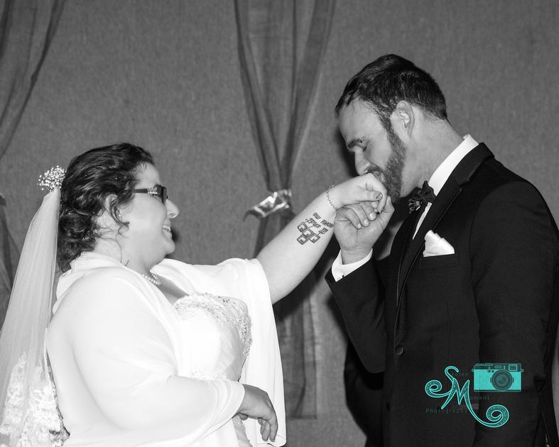 groom kissing bride's hand after placing ring on her finger
