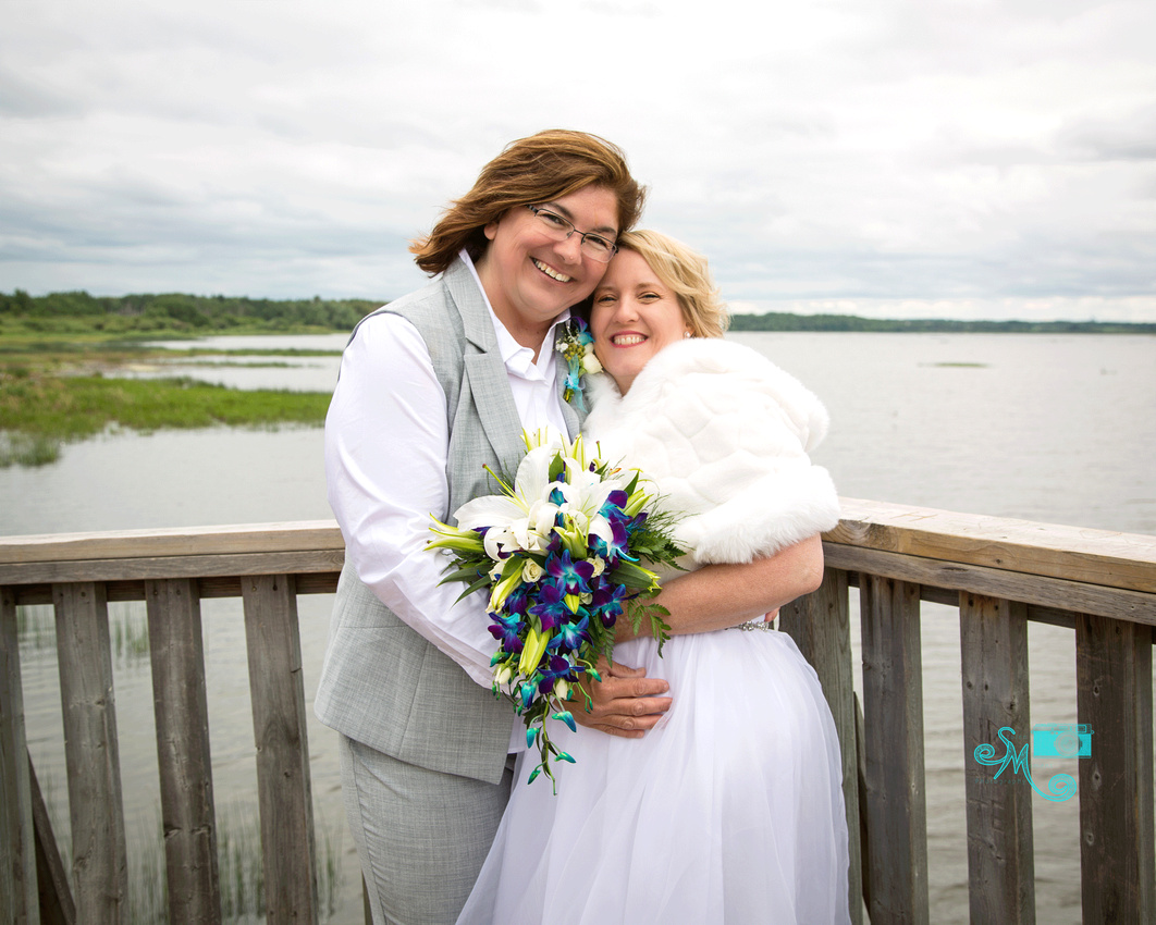 two brides snuggle and smile brightly into the camera