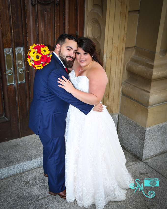 the bride and groom snuggle at the doors of the legislative building