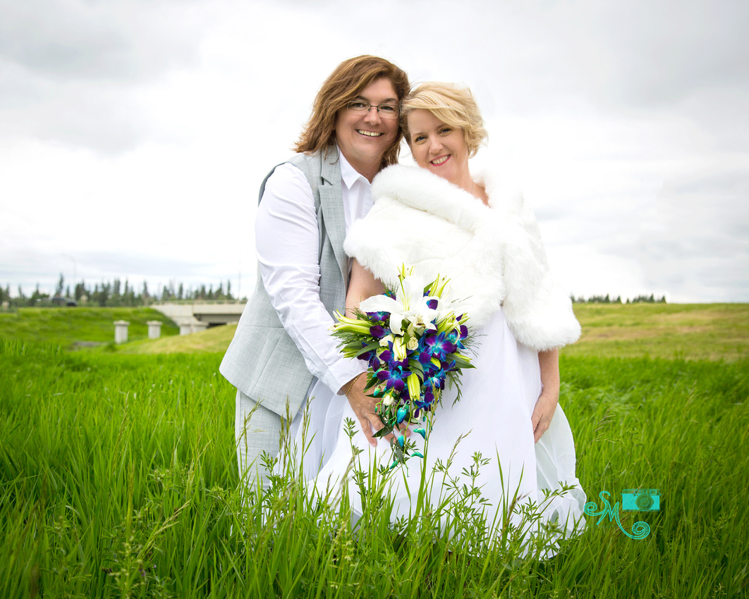 two brides pose in the tall grass