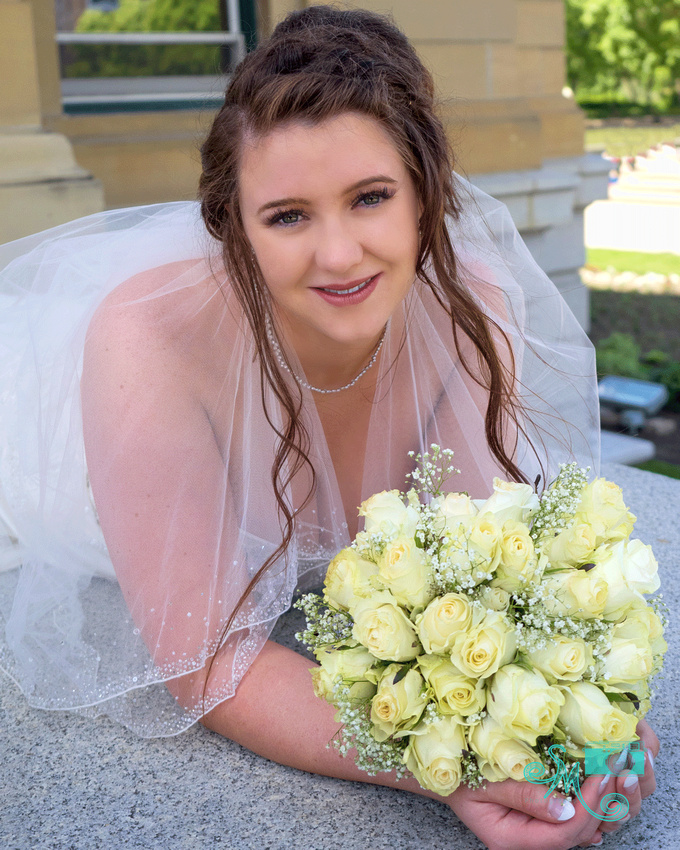 a bride lays flat on a ledge smiling into camera