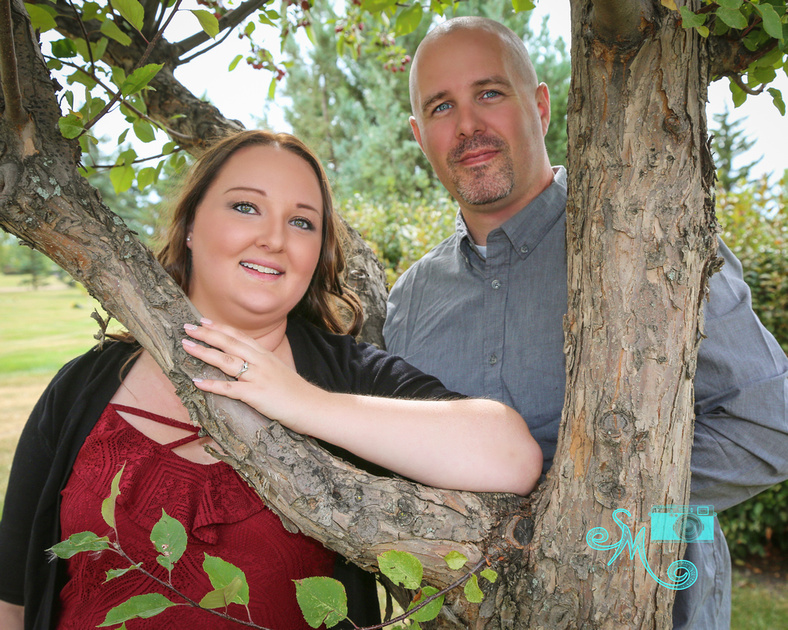 A woman and her fiance pose together at a tree