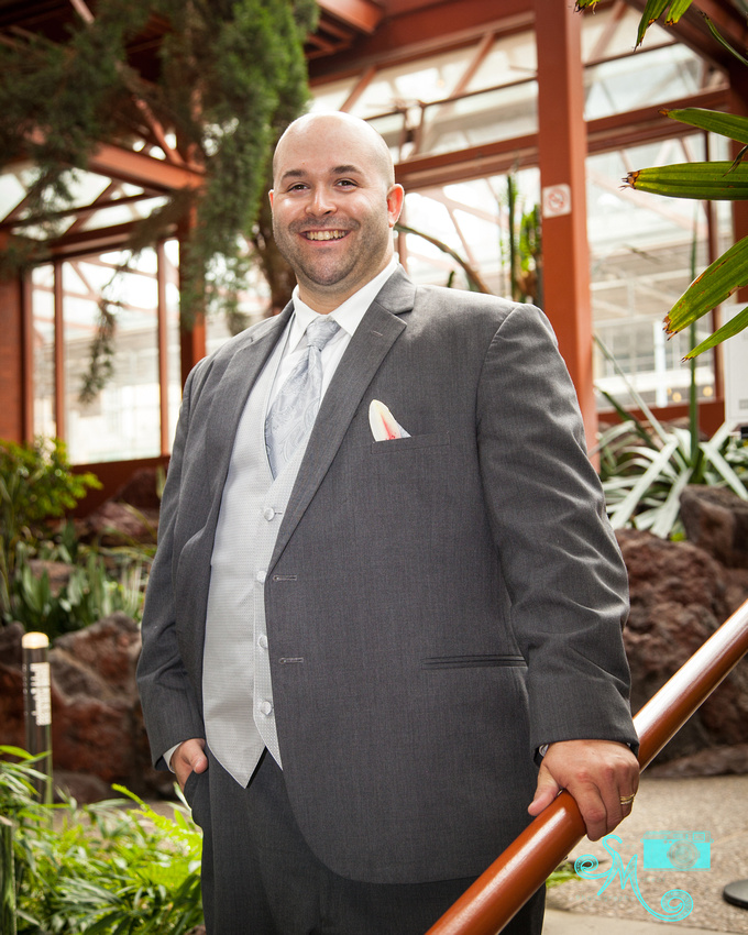 The groom stands in front of plants in the Lee Pavilion