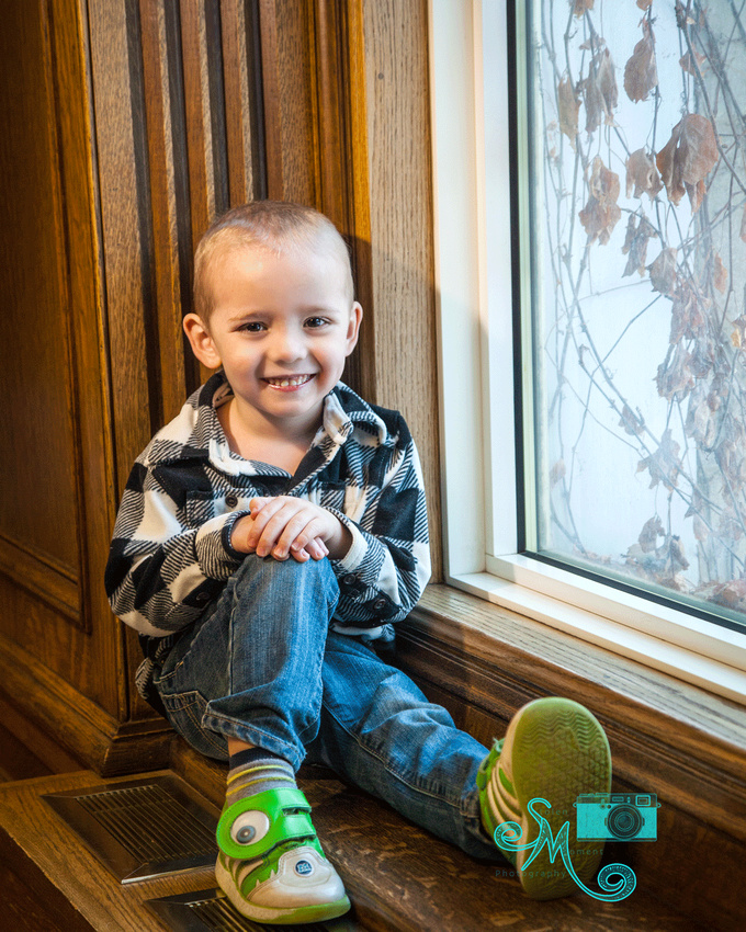 a little boy sits on a window sill smiling at the camera
