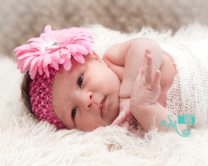 a newborn lays on her side looking into the camera