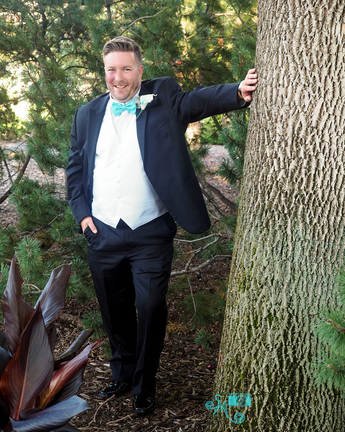 a groom leans on a tree striking a pose