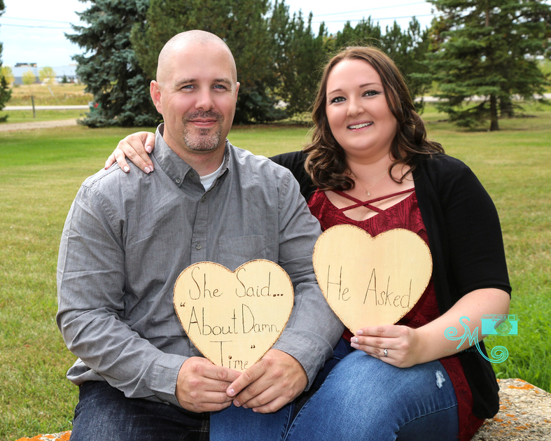 """A man and his fiance hold up """"he asked"""" and """"she said"""" signs"""